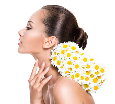 Young beautiful woman with posy flowers touching neck - isolated on white background LANG_EVOIMAGES
