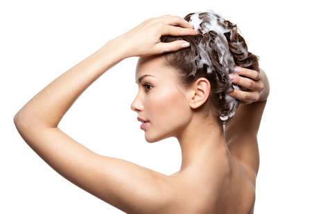 Beautiful woman soaping the brown hair - on white background LANG_EVOIMAGES
