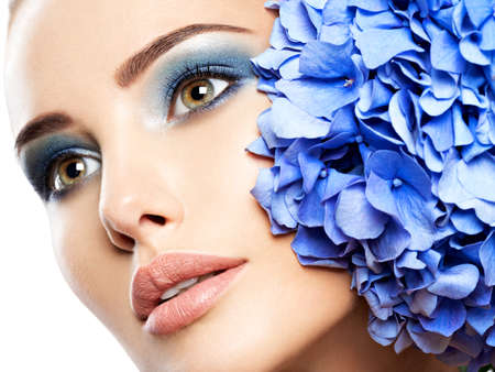 Makeup Face Flower Blue Woman Fashion. Closeup face of young beautiful woman with a blue makeup of eyes LANG_EVOIMAGES