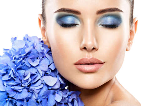 Makeup Face Flower Blue Woman Fashion. Closeup face of young beautiful woman with a blue makeup of eyes.   - isolated on white background