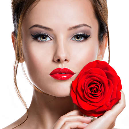 Closeup face of an young beautiful woman with bright  eye makeup  and red lipstick. Portrait of a pretty tender adult girl with creative hairstyle and red rose in hands -   isolated on white