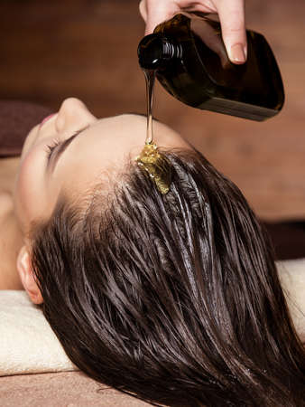 Cosmetologist pours balm for hair on the head of the woman. Spa treatments. Beauty treatment. Spa salon