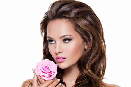 Face of an young beautiful caucasian woman with long brown curly hairs and pink lipstick. Portrait of a pretty gentel fashion model with pink rose flower in hand -   isolated on white LANG_EVOIMAGES