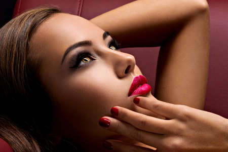 Beautiful seductive woman with dark brown eye makeup and bright red lips lying on the sofa LANG_EVOIMAGES