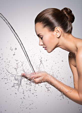 healthy body: Closeup portrait of a caucasian woman washing her clean face with water