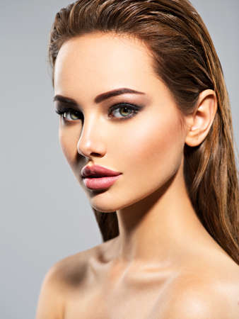 Beauty face of the young beautiful woman. Gorgeous female portrait with slicked brown hair. Young adult girl with healthy skin. Pretty lady with fashion eye makeup.