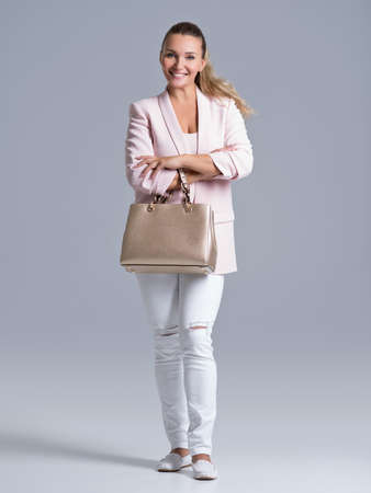 Full portrait of an young happy woman with handbag posing at studio LANG_EVOIMAGES