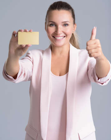 Cheerful excited surprised young woman with credit card and thumb up over white background