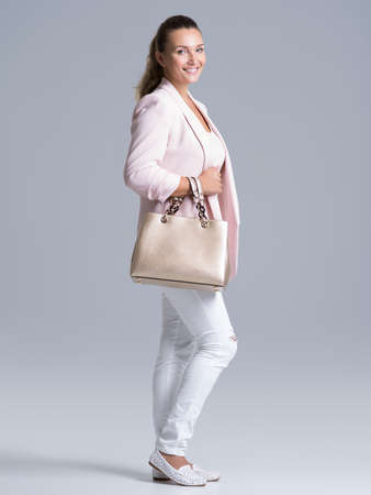 Full portrait of an young happy woman with handbag posing at studio.
