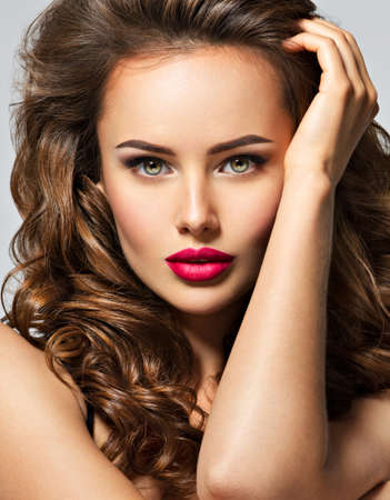 Beautiful woman with long brown curly hair. Closeup portrait with a pretty face of the young girl. Fashion model with red lip posing at studio.