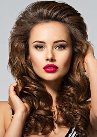 Young pretty woman with long hair. Closeup portrait with a pretty face of the young girl. Fashion model with red lip posing at studio.