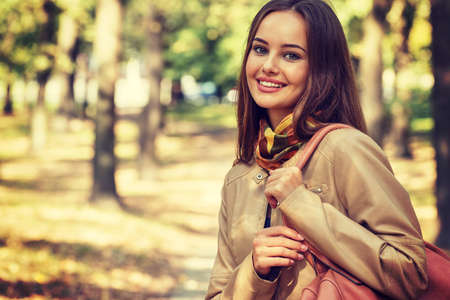 Young  girl smiling in autumn scenery. Beautiful woman outdoors in sunny day. LANG_EVOIMAGES