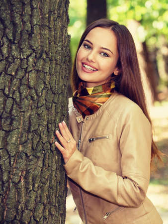 Young  girl smiling in autumn park. Beautiful happy woman outdoors in sunny day. LANG_EVOIMAGES