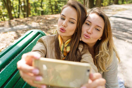Two young girls having fun and taking photos making selfie on smartphone. Beautiful happy women outdoors in sunny day in park autumn. LANG_EVOIMAGES