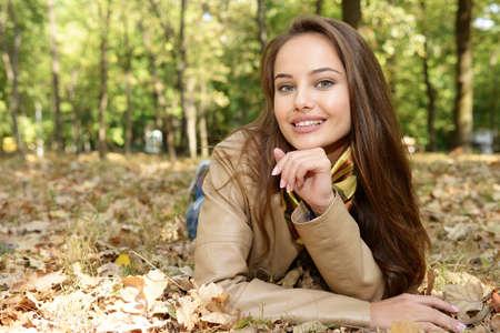 Ragazza che sorride nel paesaggio di autunno che si trova giù le foglie. Bella donna all'aperto in giornata di sole. Archivio Fotografico - 87499064
