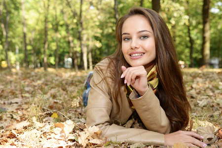 Young  girl smiling in autumn scenery lying down the leaves. Beautiful woman outdoors in sunny day.