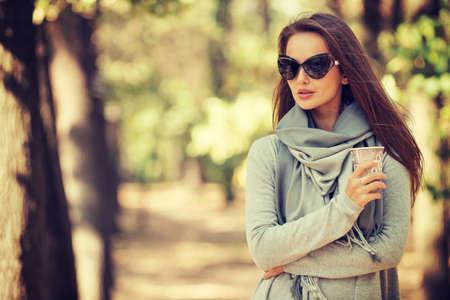 Mooi glimlachend meisje in modieuze manierkleren in de herfstpark met kop van koffie. Mooie vrouw in openlucht in zonnige dag.