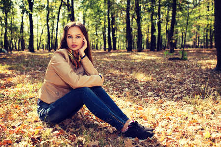 Young  girl in autumn scenery. Beautiful woman outdoors in sunny day. Pretty female with calm emotions in fall landscape.