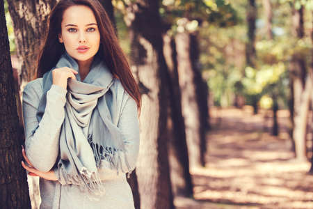Beautiful smiling girl in stylish fashion clothes in autumn Park.  Beautiful woman outdoors in sunny day. LANG_EVOIMAGES