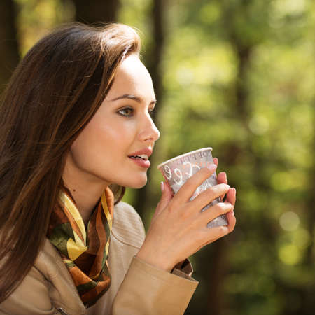 Beautiful young girl  drinks coffee  autumn park. Beautiful woman  in fall sunny day with cup of tea.
