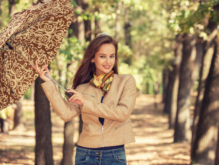 Young  girl smiling in autumn with umbrella. Beautiful woman outdoors in sunny day. Portrait of a happy female over fall landscape.