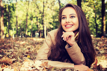 Young  cute girl smiling in autumn scenery. Beautiful woman outdoors in sunny day.