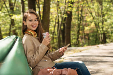 Beautiful woman outdoors in sunny autumn day with mobile phone.