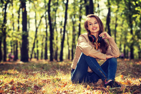 Young  girl smiling in autumn scenery sits on the ground. Beautiful woman outdoors in sunny day. LANG_EVOIMAGES