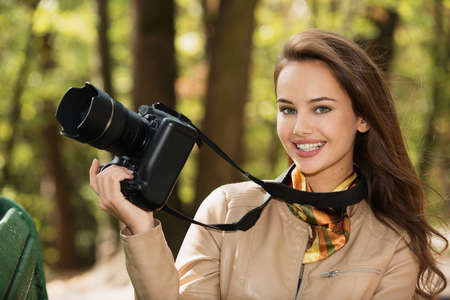 woman is a professional photographer with photo camera outdoor. Young girl taking photo outdoors with digital camera