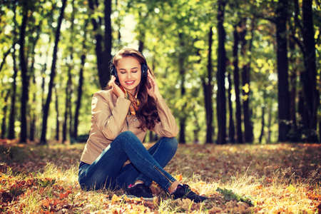 repose: Young  girl smiling and listening music in autumn park in the headphones. Beautiful woman relaxing outdoors in sunny day.