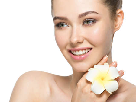 only 1 woman: Beautiful face of an young cheerful woman with flower near face, clean healthy skin - isolated on white. Skin care concept.