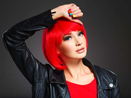 Closeup face of a beautiful  girl with bright multicolor nails. Gorgeous and stunning  woman with bob hairstyle red color. Fashion model in black leather jacket with creative style posing at studio.