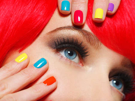 Closeup eyes of a girl with bright multicolor nails. woman with brown stylish eye makeup of eyes.