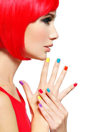 Closeup face of a beautiful  girl with bright multicolor nails. Profile portrait of a Gorgeous and stunning  woman with bob hairstyle red color. Stock Photo