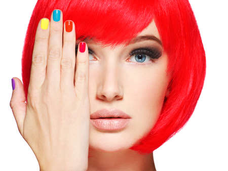 Closeup face of a beautiful  girl with bright multicolor nails. Gorgeous and stunning  woman with bob hairstyle red color.