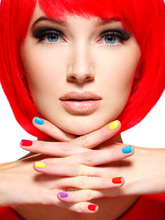 beautiful face of a girl with stylish multicolor nails. Gorgeous and stunning  woman with bob hairstyle red color. Stock Photo