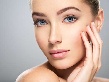 Jonge Kaukasische vrouw met mooi gezicht - dat op wit wordt geïsoleerd. Huidverzorging concept. Stockfoto