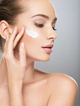 Belle jeune femme obtient la crème dans le visage. Concept de soins de la peau. Superbe femme caucasienne avec une peau propre et parfaite. Portrait d'une jolie fille aux yeux bleus, agrandi.