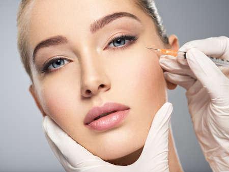 Femme, obtenir une injection cosmétique de botox dans la joue, agrandi. Femme dans un salon de beauté. clinique de chirurgie plastique. LANG_EVOIMAGES