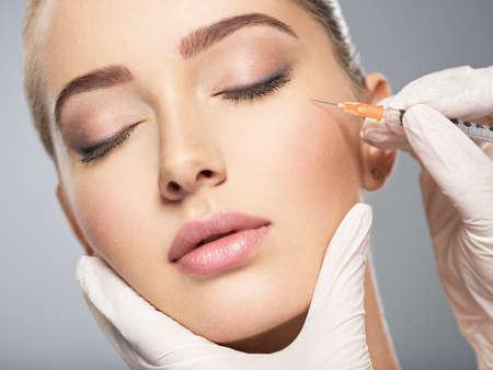 Femme obtient une injection cosmétique de botox près des yeux, se ferme. Femme dans le salon de beauté. clinique de chirurgie plastique.