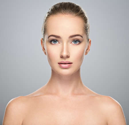Beautiful face of young caucasian woman with perfect health clean skin.  Skin care treatment. Portrait of an Attractive girl  with blue eyes, closeup. Pretty  and sexy female with stunning look. LANG_EVOIMAGES