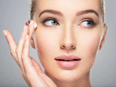 Belle jeune femme obtient de la crème près des yeux. Concept de soins de la peau. Superbe femme caucasienne avec une peau propre et parfaite. Portrait d'une jolie fille aux yeux bleus, agrandi.
