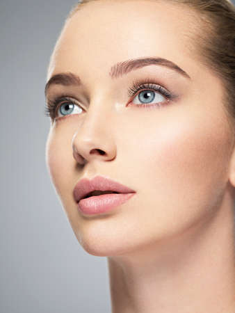 Beautiful face of young caucasian woman with perfect health clean skin.  Skin care treatment. Profile Portrait of an Attractive girl  with blue eyes, closeup. Pretty  and sexy female with stunning look.
