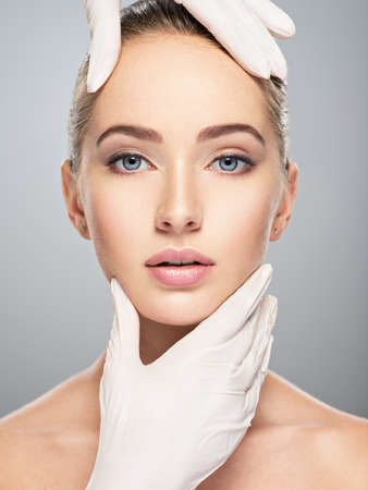 Vérification de la peau du visage avant la chirurgie plastique. Esthéticienne, toucher le visage de la femme. Forme parfaite du visage féminin.