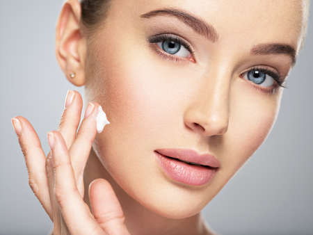 Beautiful young woman gets cream in the face. Skin care concept. Stunning caucasian woman with perfect health clean skin. Portrait of an Attractive girl  with blue eyes, closeup.