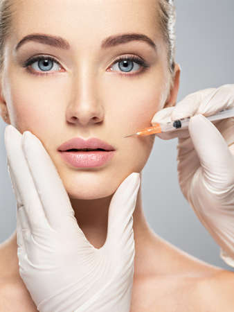 Woman getting cosmetic injection of botox in cheek, closeup. Woman in beauty salon. plastic surgery clinic. LANG_EVOIMAGES