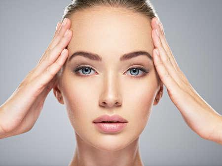 ottimo: Bella faccia di giovane donna caucasica con perfetta pelle pulita della salute. Trattamento della cura della pelle. Ritratto di una ragazza attraente con gli occhi azzurri, closeup. Femmina graziosa e sexy con un look sbalorditivo. LANG_EVOIMAGES