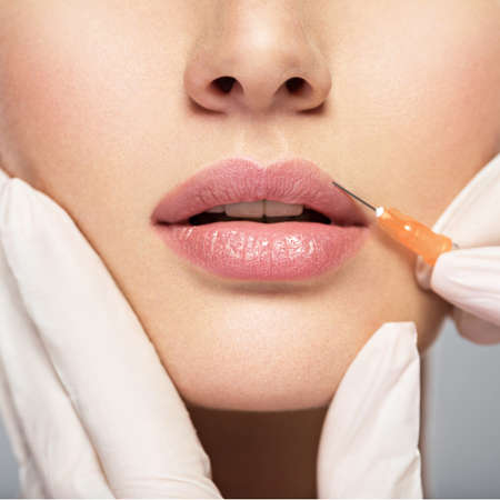 young woman gets botox injection in her lips. Woman in beauty salon. plastic surgery clinic. LANG_EVOIMAGES