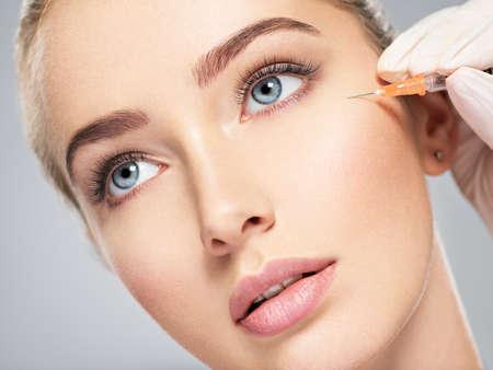 Femme recevant une injection cosmétique de botox près des yeux, agrandi. Femme dans un salon de beauté. clinique de chirurgie plastique.