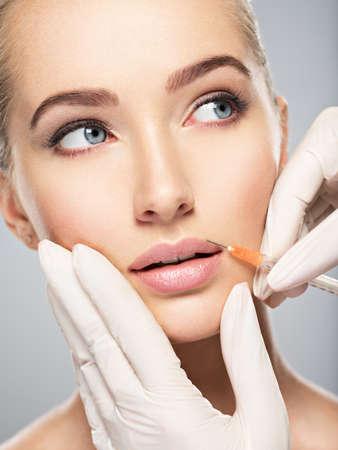 jeune femme reçoit une injection de botox dans ses lèvres. Femme dans un salon de beauté. clinique de chirurgie plastique. LANG_EVOIMAGES